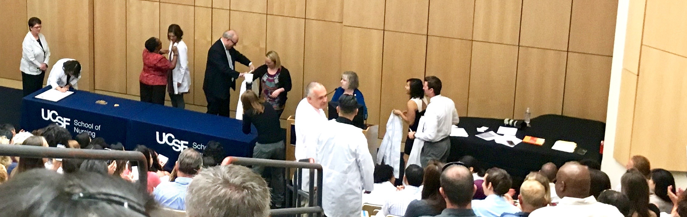 2016 MEPN students approach the podium and stage to receive their white coats and pins.