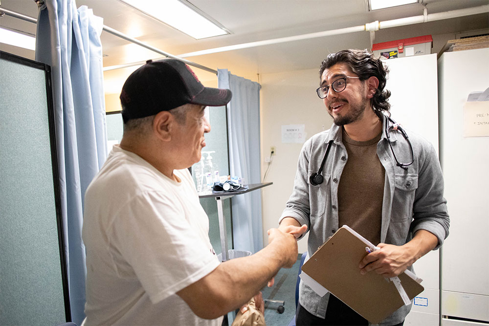 Frank Molina supports a client at the Homeless Clinic